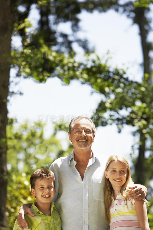 Nonno con i nipoti in parco fotografie stock