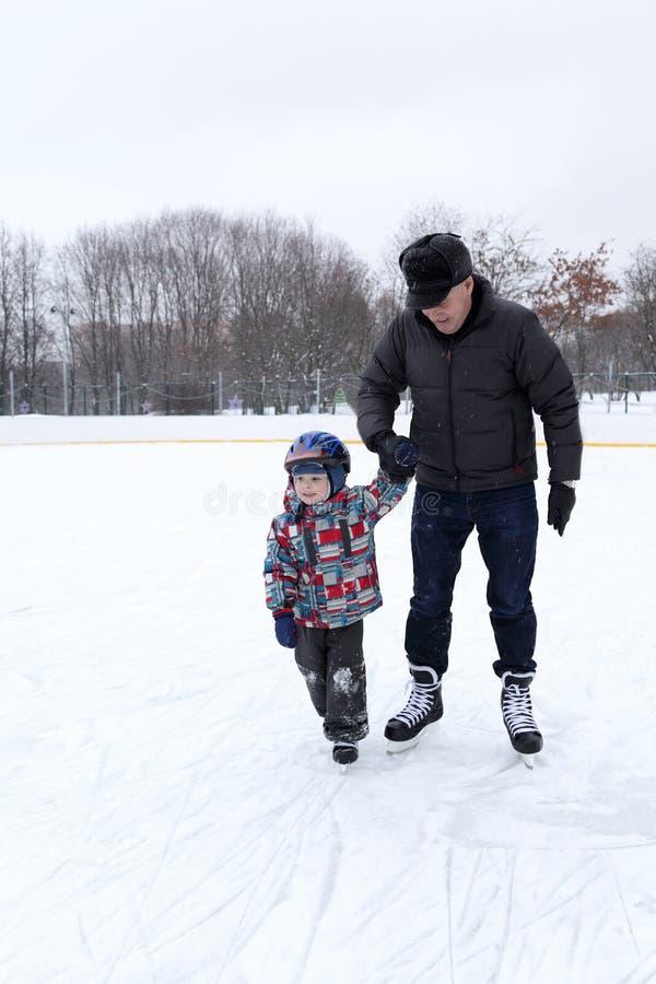 Nonno con il nipote alla pista di pattinaggio fotografie stock