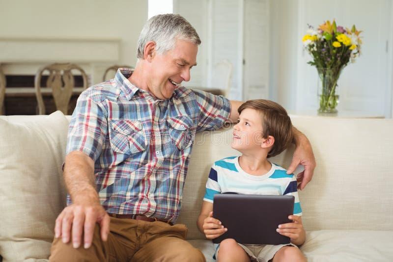 Nonno con il suo nipote che per mezzo della compressa digitale sul sofà fotografie stock