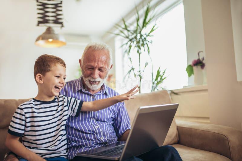 Nonno e nipote che per mezzo del computer portatile fotografie stock