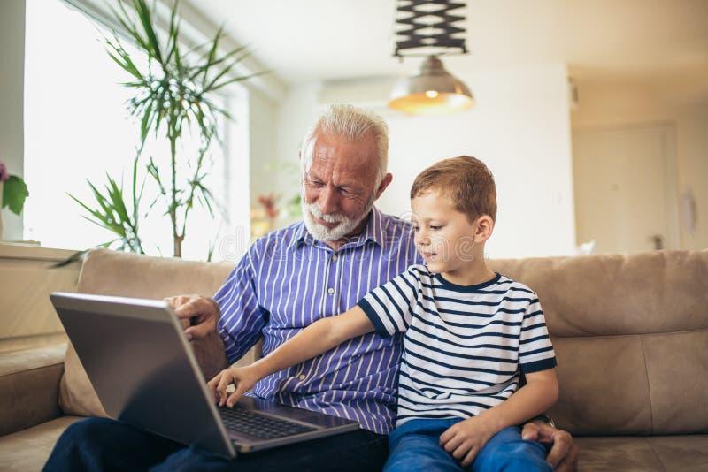 Nonno e nipote che per mezzo del computer portatile fotografia stock