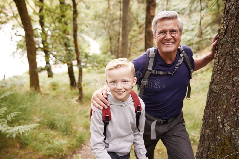 Nonno e nipote che prendono una rottura mentre facendo un'escursione insieme in una foresta, fine su, sorridente alla macchina fo fotografie stock