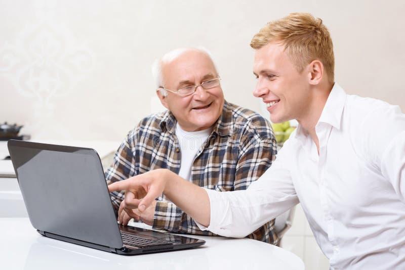 Download Nonno E Nipote Che Si Siedono Con Il Computer Portatile Fotografia Stock - Immagine di cucina, invecchiato: 55351562