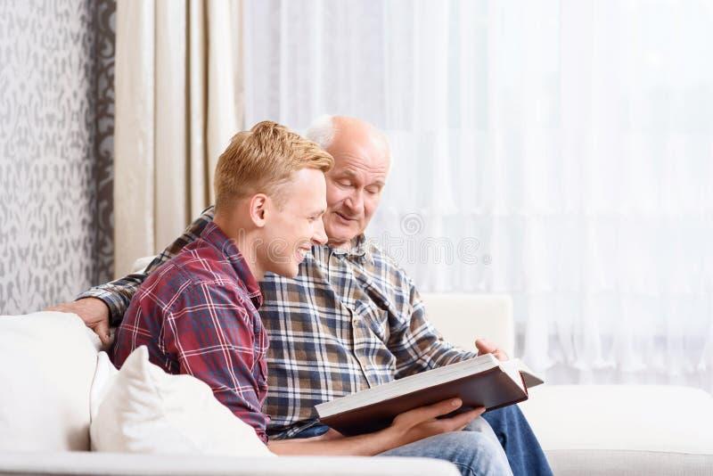 Download Nonno E Nipote Che Si Siedono Con L'album Fotografia Stock - Immagine di faccia, cheerful: 55351462