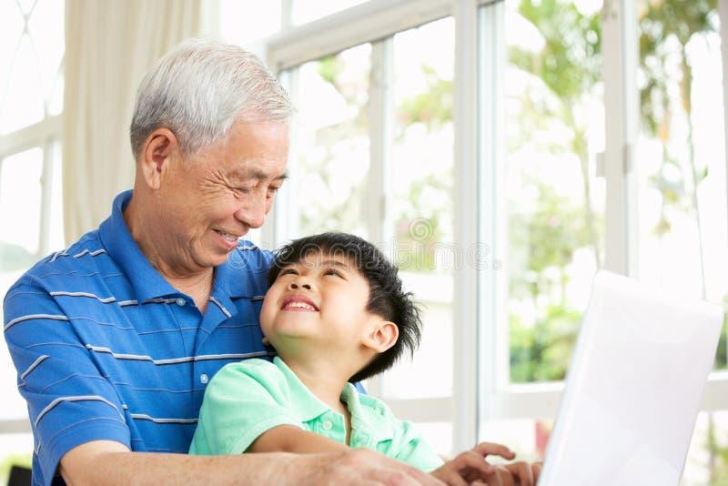 Nonno e nipote cinesi che per mezzo del computer portatile immagine stock libera da diritti