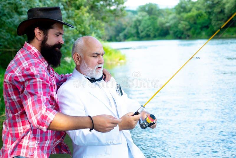 Nonno e nipote felici con le canne da pesca sull'ancoraggio del fiume angler Nonno e ragazzo che pescano insieme Fondo verde degl immagine stock