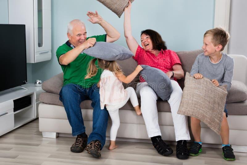 Nonno e nipoti che hanno lotta di cuscino fotografia stock