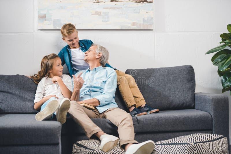 Nonno e nipoti che si siedono sul sofà immagine stock