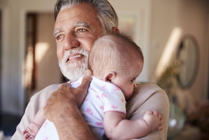 Nonno ispano che tiene il suo nipote del bambino, di gran lunga, fine su fotografia stock libera da diritti