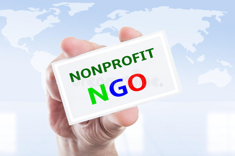 Nonprofit NGO concept. Hand holding nonprofit NGO card concept on world map background stock photos