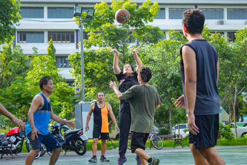 Nonthaburi在泰国,男人和妇女打在平均观测距离的篮球 免版税库存图片