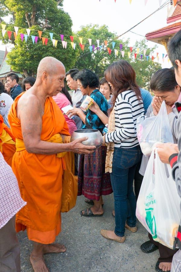 Nonthaburi TAJLANDIA, Jan, - 1, 2014    Niezidentyfikowanym mnichom buddyjskim dają karmowej ofiarze od ludzi zdjęcie royalty free