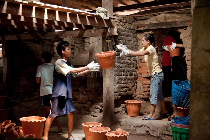 Nonthaburi Tajlandia, Kwiecień, - 26, 2015: Pracownicy niesie glinianych garnki z kiln Doniczkowe rośliny potrzebują czas palić w zdjęcie stock