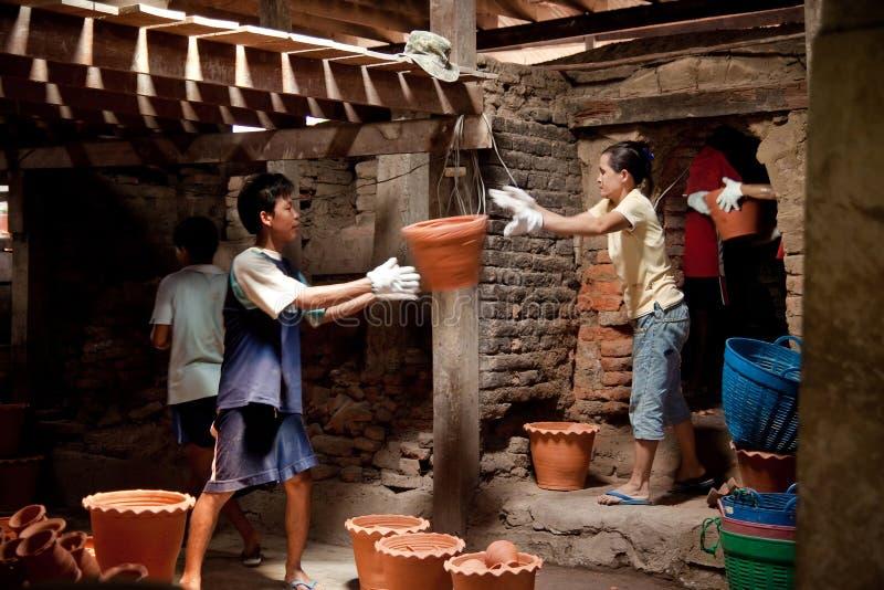 Nonthaburi Thailand - April 26, 2015: Arbetare som bär lerakrukor ut ur brännugnen Inlagda växter behöver tid att bränna i pannor arkivfoto