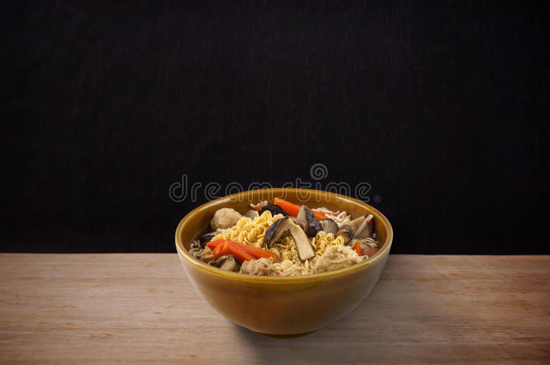 Noodle in brown bow on woodenl in over dark tone stock photos