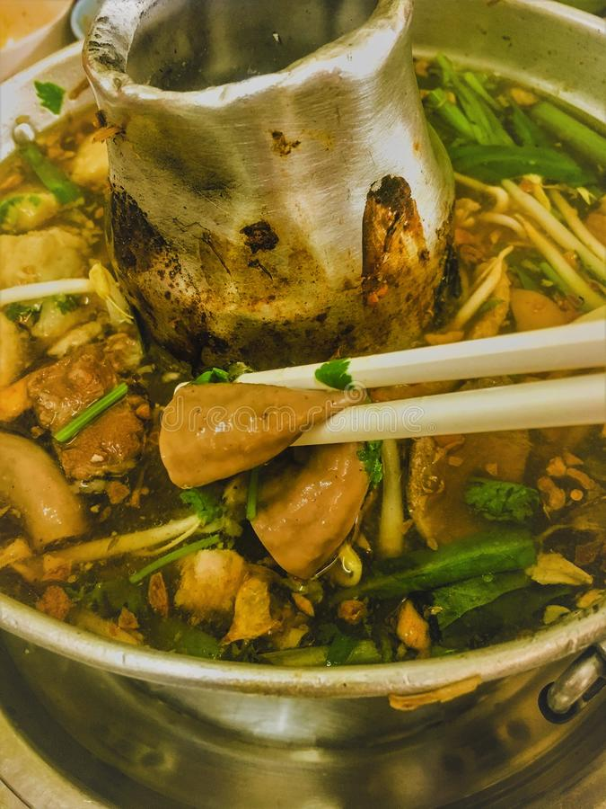 Noodle with pork soup in hot pot and fire below pot royalty free stock photos
