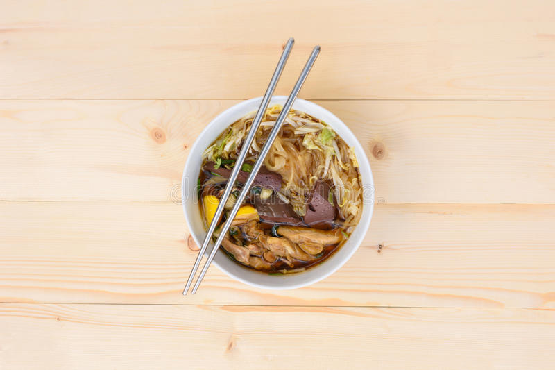 Noodle soup. With chopsticks in bowl on a wooden table, top view, Thai local food stock image