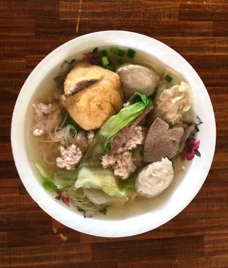 Noodle soup with minced pork ball and fish paste. This is typical common dish in Southeast Asia served in traditional old school bowl. Ingredients include stock photos