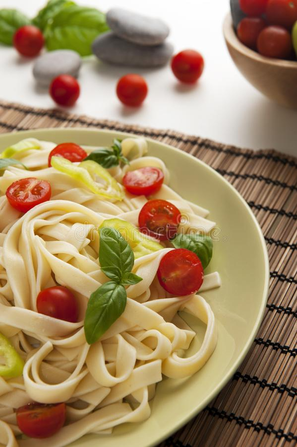 Noodles. With cherry tomatoes, green pepper and basil stock photo