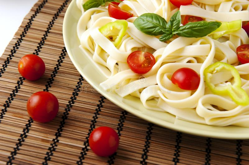 Noodles. With cherry tomatoes, green pepper and basil stock images