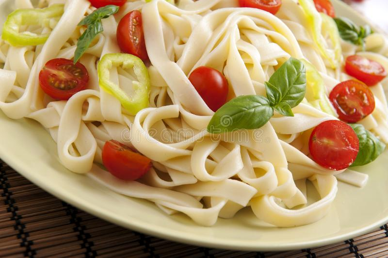 Noodles. With cherry tomatoes, green pepper and basil stock photos