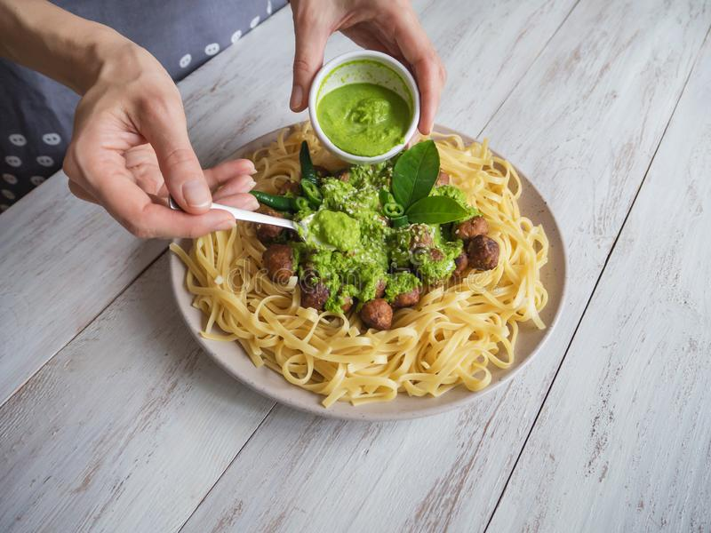 Noodles with meatballs with spinach sauce. royalty free stock photography