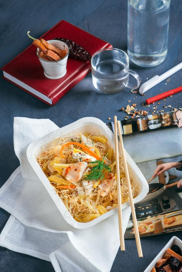 Noodles with sour sauce in disposable tableware royalty free stock photography