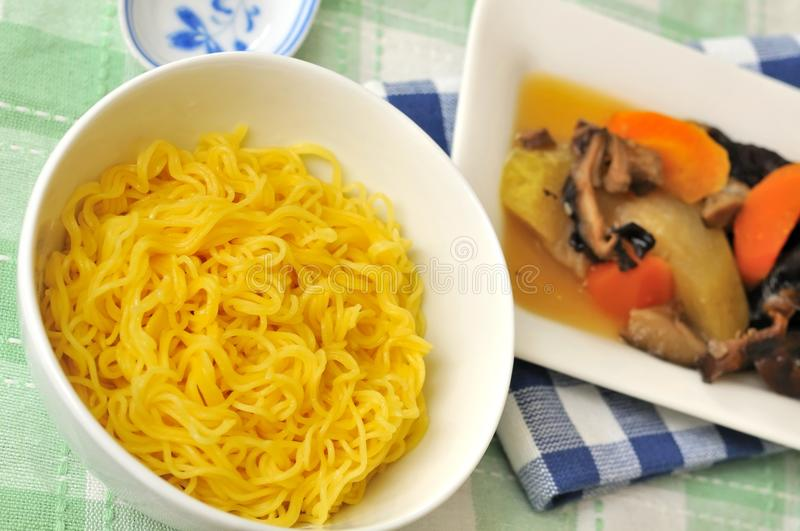 Noodles with vegetable side dish. Plain noodles with Chinese style vegetable side dish cuisine in background royalty free stock image