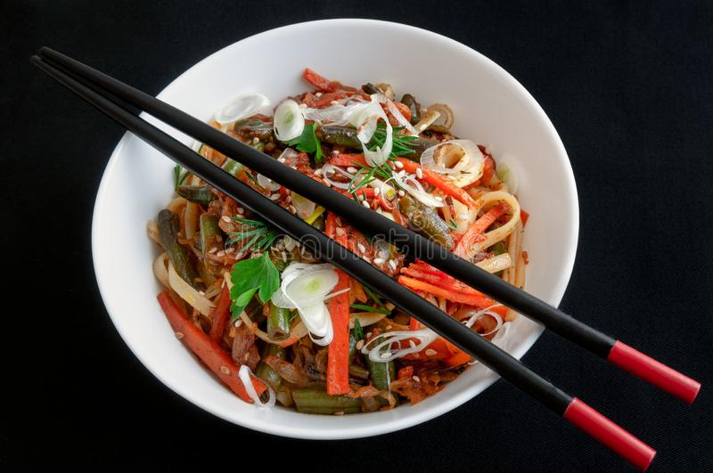 Noodles wok, with vegetables, herbs and sesame. In a white round plate. On top of the plate, Chinese sticks are black and red. stock photos