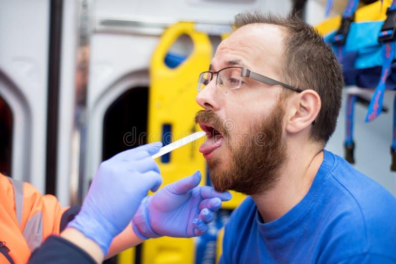 Noodsituatie arts in de ziekenwagen die een patiënt onderzoeken stock fotografie
