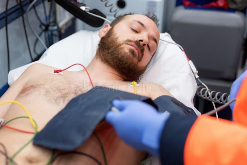 Noodsituatie arts die bloeddruk van een patiënt in de ziekenwagen controleren stock fotografie