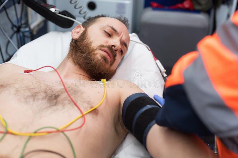 Noodsituatie arts die bloeddruk van een patiënt in de ziekenwagen controleren royalty-vrije stock afbeelding