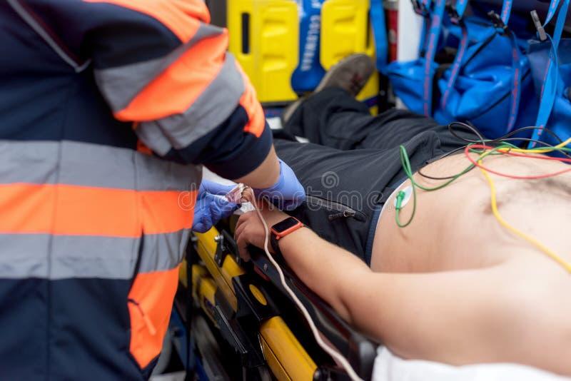 Noodsituatie arts die impuls van een patiënt in de ziekenwagen controleren royalty-vrije stock foto
