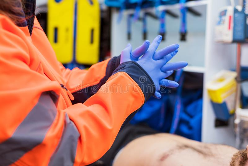 Noodsituatie arts die op handschoenen in ziekenwagen zetten stock fotografie