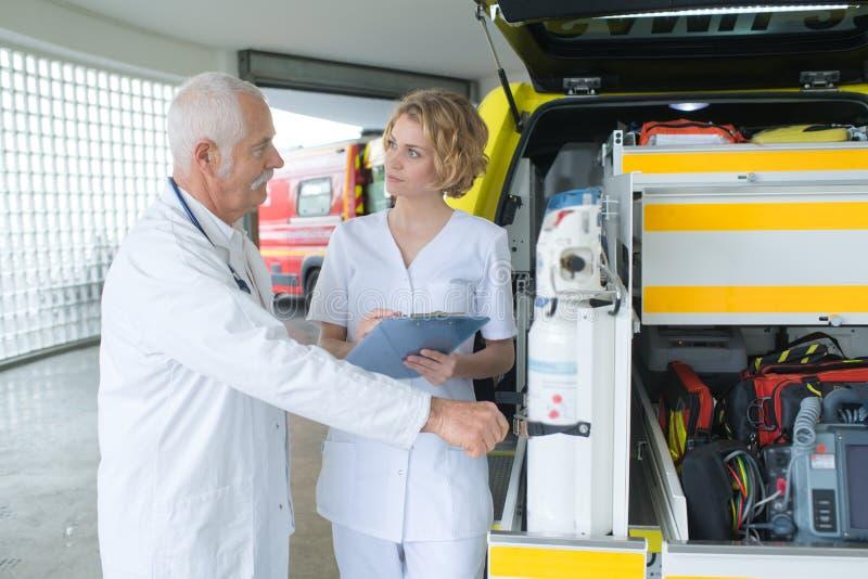 Noodsituatiearts en verpleegster die zich vooraan ziekenwagenauto bevinden stock afbeeldingen