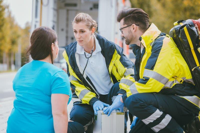 Noodsituatiedokters die aan verwonde vrouw spreken stock afbeeldingen