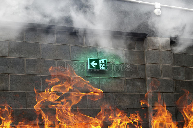Noodsituatienooduitgang op de steenmuur met brand en rook stock foto