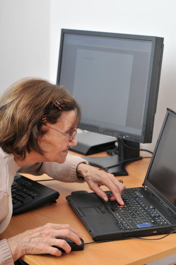 Nooit oud genoeg - hogere vrouw met computer stock afbeeldingen