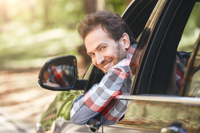 Nooit word zo bezig het maken van het leven dietot u vergeet om het leven te maken Glimlachende mens die uit het venster, terwijl stock afbeeldingen