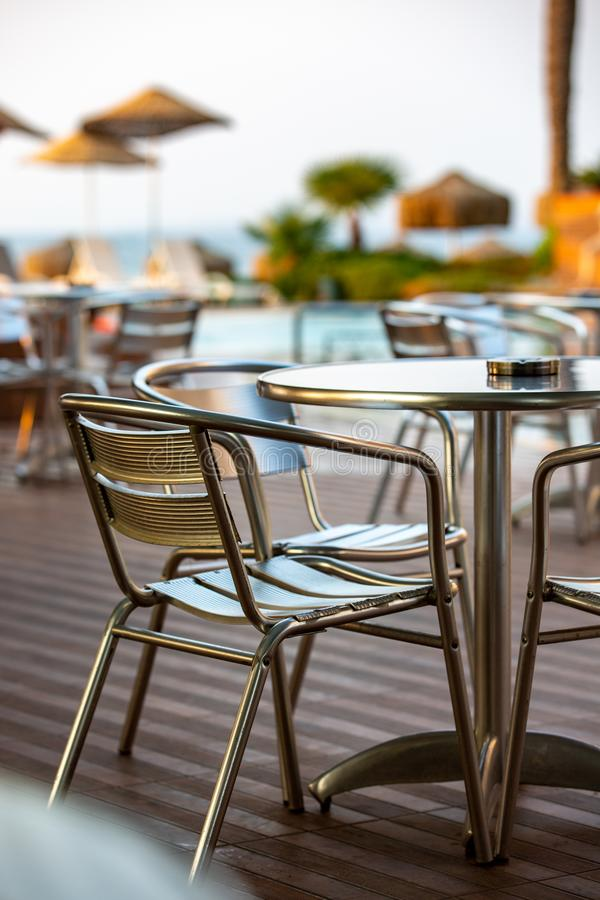 Nook of street cafee with several metal chairs and tables near sea. stock image