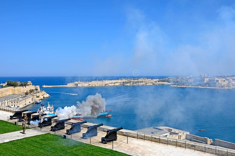 The Noon Gun overlooking the Grand Harbour, Valletta. Soldiers firing the cannons for the Noon Gun in Upper Barrakka Gardens with views across the Grand Harbour stock photos