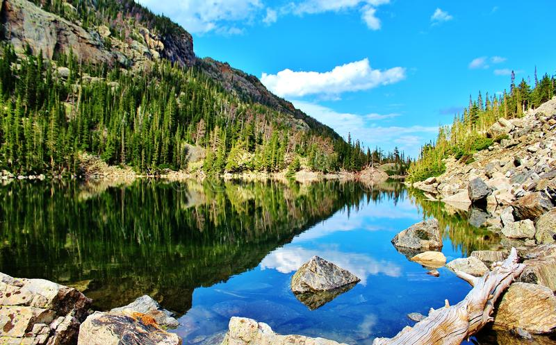 Noon lake reflection. High noon of emarald lake in rocky mountain national park, the other side of the lake where visitors don't get to very often royalty free stock image