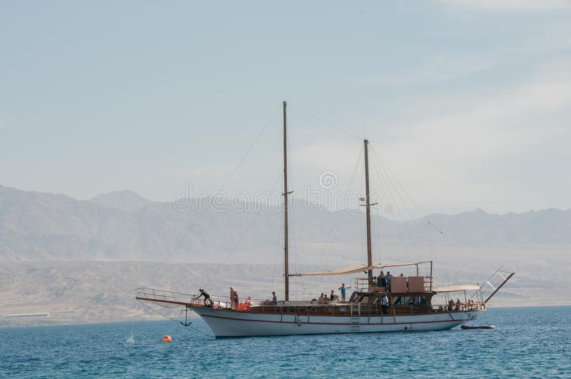 Noon, a yacht in the Red Sea. Against a backdrop ofred- hot mountains royalty free stock photography