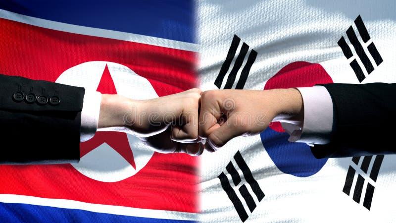Noord-Korea versus het conflict van Zuid-Korea, vuisten tegen vlagachtergrond, diplomatie stock fotografie
