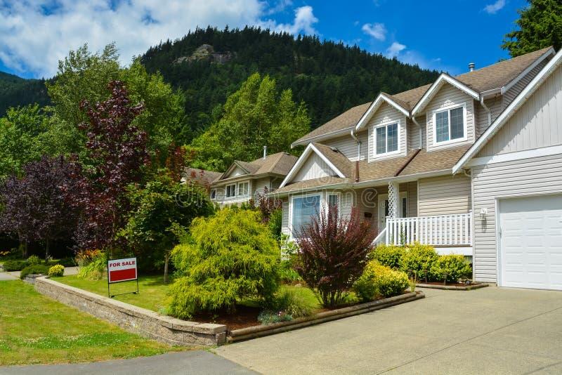 Noordamerikaans huis op plattelandsgebied met keurig gemodelleerde vooryard voor verkoop royalty-vrije stock afbeelding
