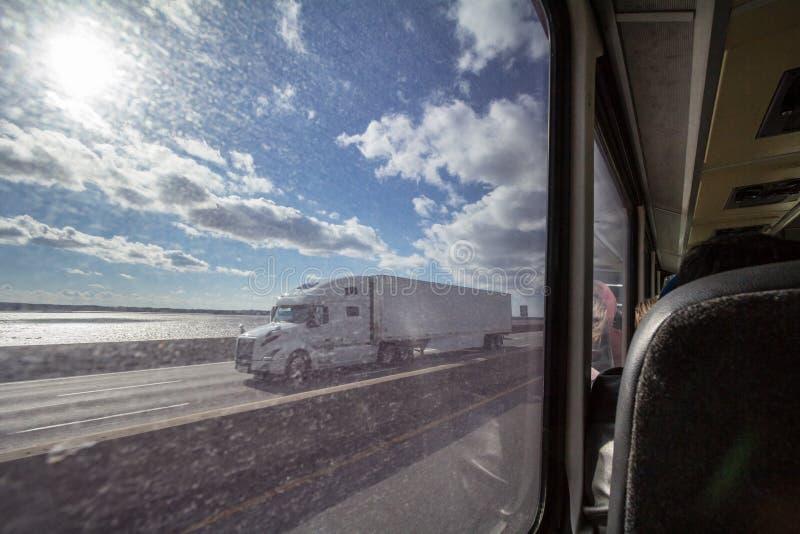 Noordamerikaanse die vrachtwagen van het grote venster van een bus op een weg van Quebec in de voorsteden van Montreal wordt gezi stock foto's