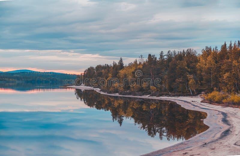 Noordelijk Finland, zonsondergang/zonsopgang bij het meer met een kalm water en zandstrand stock foto
