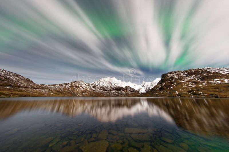 Noordelijke lichten achter dunne wolken over een bergketen royalty-vrije stock fotografie