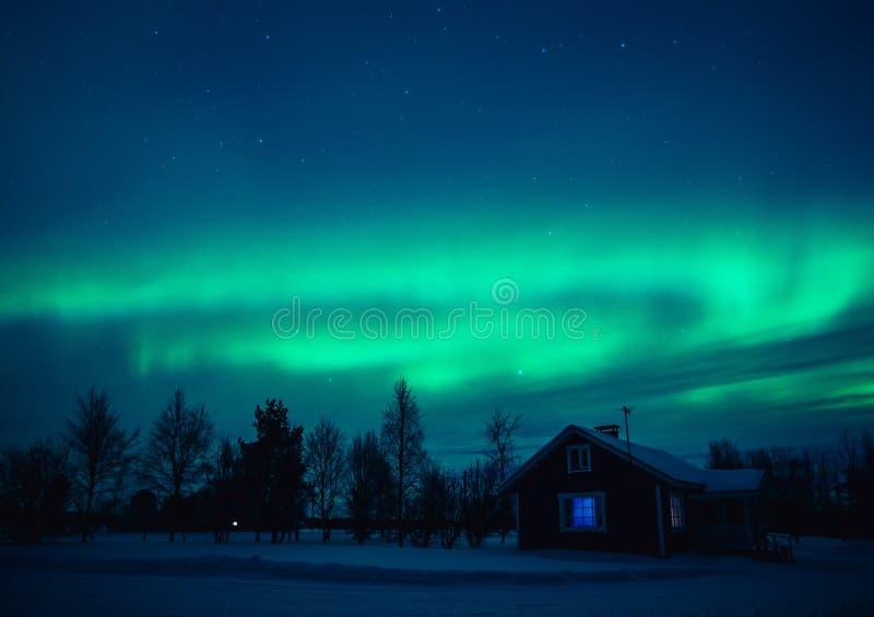 Noordelijke lichten Aurora Borealis over plattelandshuisje in het dorp van Lapland finland stock afbeeldingen
