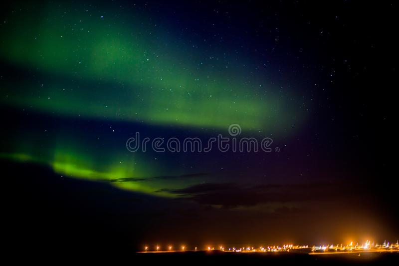 Noordelijke lichten over een stad in IJsland stock afbeeldingen
